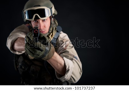 Soldier with gun against black background.