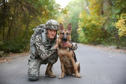 Soldier with military working dog on asphalt road in forest