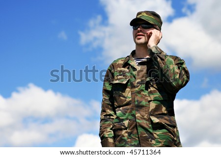 Soldier with Mobile Phone, Military Man in Camouflage Army Uniform calling by cellular phone over blue sky