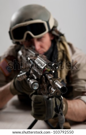 Soldier with rifle against white background. Shallow depth of field.
