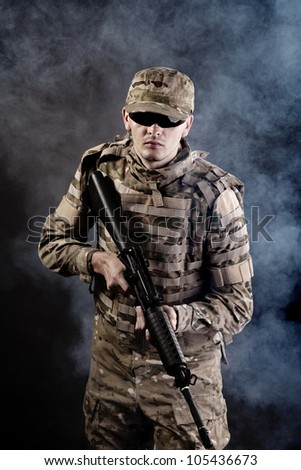 Soldier with rifle on a black background with white smoke