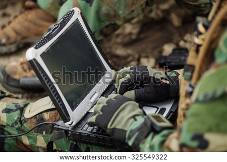 Soldier works on his laptop