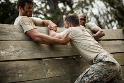 Soldiers helping man to climb wooden wall in boot camp