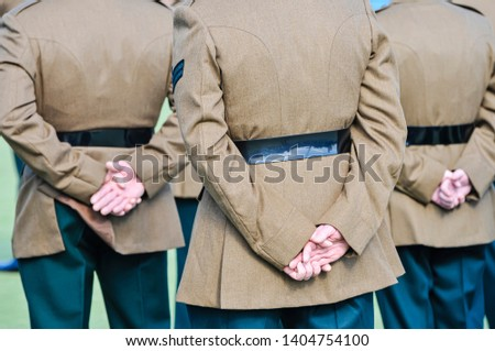 Soldiers hold their hands behind their backs while on parade