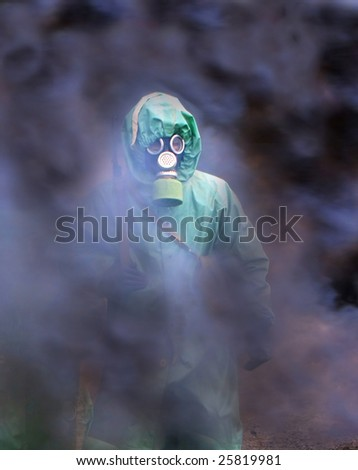 soldiers in chemical protection suites walking through the smoke