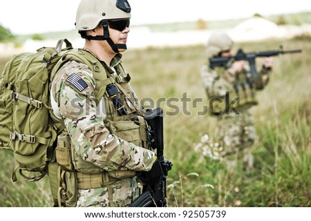 Soldiers  in full gear patrol the area in the desert