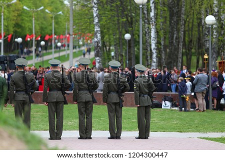soldiers in uniform at memorial cemetery during memorial ceremonies for those killed in wars, tradition of Patriotic education, disciplined soldiers on a solemn March past graves of dead colleagues