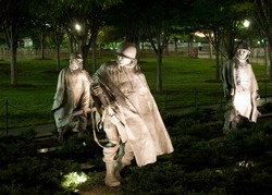 Soldiers of the Korean War Memorial in Washington, DC move under cover of darkness, as they would have moved during the war. Night lighting provides ghostly shadows on the statues faces.