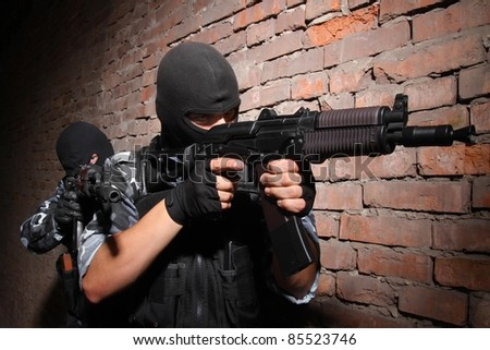Soldiers or terrorists in black masks and heavy ammunition with automatic rifles