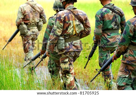 Soldiers patrol in army uniform - stock photo