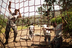 Soldiers performing training exercise on net in bootcamp