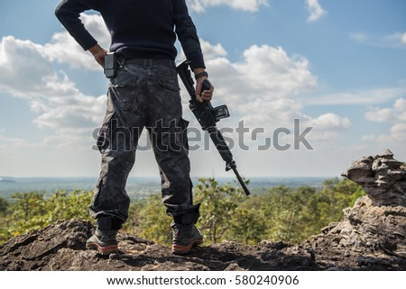 Soldiers with rifles guard duty on a rock mountain hot sun. #580240906