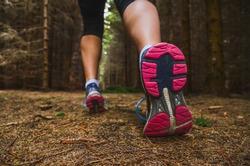Sole of running shoe in dark forest - run, sport active concept photo