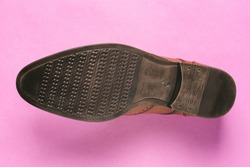 Sole of the Shoe is isolated on a purple background. The sole of a classic mens Shoe close-up. Top view, flat layout