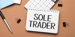 sole trader on notepad with pen, glasses and calculator