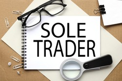 SOLE TRADER, text on white notepad on craft background