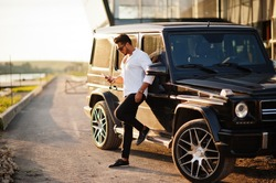 Solid asian man in white shirt and sunglasses posed near black mafia suv car with mobile phone.