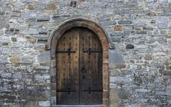 Solid castle wooden door arch door and stone wall