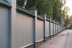 Solid concrete fence. Fence and paved road. Fenced territory, private property.