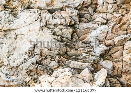 Solid limestone rock texture with muliple cracks, taken near the beach on a sunny day