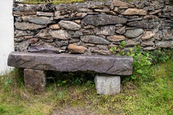 Solid stone bench by stone wall fence. Future proof design. House hold time made for future generation. Fine example of masonry craft. Old style furniture in a garden.