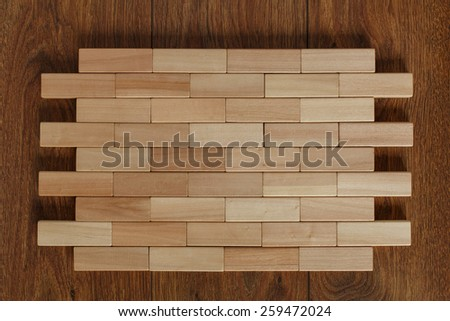 solid wall of wooden bars densely stacked wooden blocks on the floor with parquet blocks wood game (jenga)