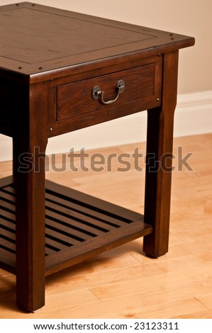 Solid wood end table against earth tone wall and hardwood floor.