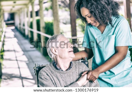Solidarity smiles between patient in a wheelchair and a nurse.