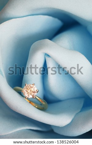 Solitaire engagement diamond ring (ideal cut) encrusted on 18K gold ring embedded in blue rose.