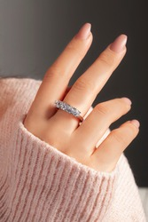 Solitaire silver ring on the finger of the lady in a pink sweater. Sterling silver jewelry with nail polish.
