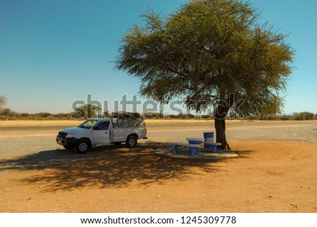 Solitary acacia tree in the middle of the african savannah with a roof tent 4x4 off-road veichle in the shadow and a pic nic area in the Kalahari, in Namibia