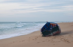 Solitary and abandoned immigrant dinghy patera boat at the Atlantic coast of south Spain