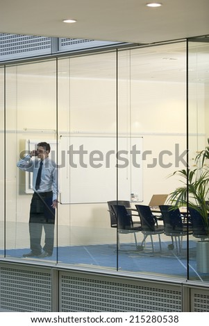 Solitary businessman standing in boardroom, using mobile phone, view through large office window