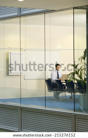 Solitary businessman working on laptop at conference table in boardroom, view through large office window