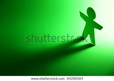 solitary cutout of a green paper person casting a shadow