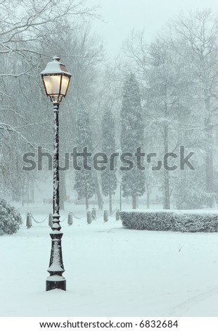 Solitary lamppost trying to shine its yellow light into a freezing cold world of snow