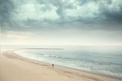 Solitary man walking on the wide beach