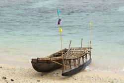 Solitary traditional wooden Outrigger on a Tropical Island Beach