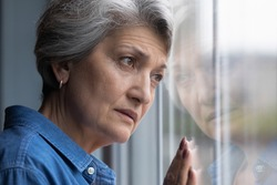 Solitude hurts so much. Cropped shot of lonely older hispanic lady lean head to window glass look at distance feel abandoned grief suffer alone. Depressed elderly woman widow mourning for gone husband
