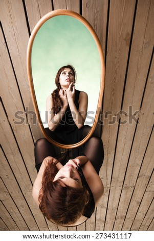 Solitude loneliness concept. Thoughtful young woman looks at the reflection in the mirror outdoors on pier