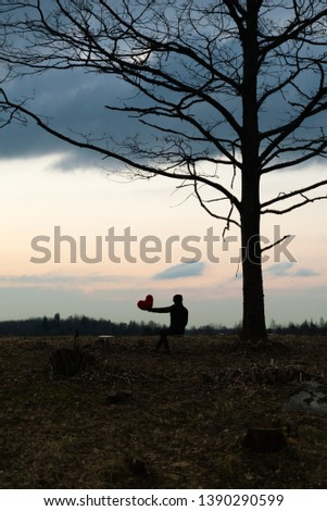 Solitude. Lonely Girl In a lonely tree against the sky. On the background of the sunrise. Red heart in hand