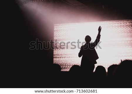 Solo artist raising hands at contemporary church conference silhouette against LED screen on stage #713602681