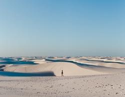 Solo female backpacker walks across the sand dunes of Lencois Maranhenses, miles and miles of sand dunes and lagoons in Maranhao, North-Eastern Brazil