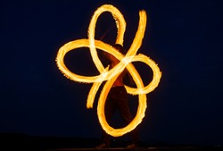 Solo fire artist perform infinite spirals by spinning flaming pois on dark sky at night outdoors, blaze.