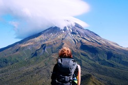 Solo traveler with backpack looking on the most iconic mountain in North Island, New Zealand. Top of Taranaki is hidden in the cloud. On top is still some snow, but on the bottom is a fresh green line