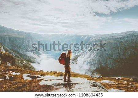 Solo traveling girl hiking with backpack in mountains adventure journey lifestyle vacations weekend getaway in Norway    #1108604435