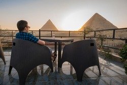 Solo Travellers. A lone man sits on the roof of a restaurant and enjoys a beautiful view of the Great Pyramids of Giza. Cairo, Egypt.