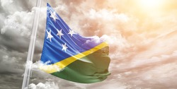 Solomon Islands national flag cloth fabric waving on beautiful grey sky.