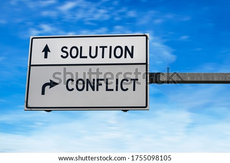 Solution versus conflict. White two street signs with arrow on metal pole. Directional road, Crossroads Road Sign, Two Arrow. Blue sky background. Foto d'archivio ©