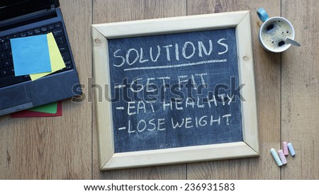 Solutions get, fit, eat healthy and lose weight written on a chalkboard at the office ストックフォト ©